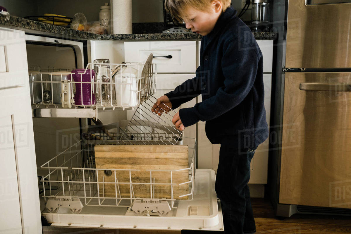 Little boy loading the dishwasher and taking responsibility in kitchen Royalty-free stock photo