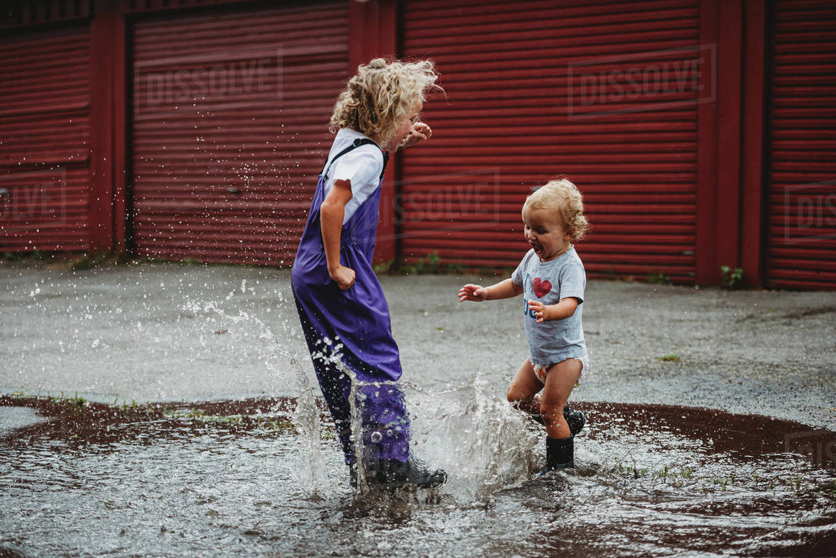 Girl and boy splashing in the water after the rain and laughing Royalty-free stock photo