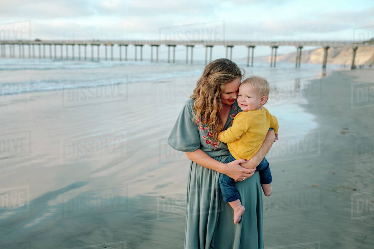 Young mother with long hair holding blonde baby at beach near pier Royalty-free stock photo