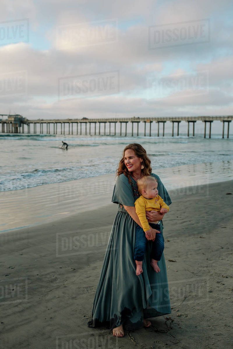 Barefoot 30 yr old mom in long dress on beach near pier holding baby Royalty-free stock photo