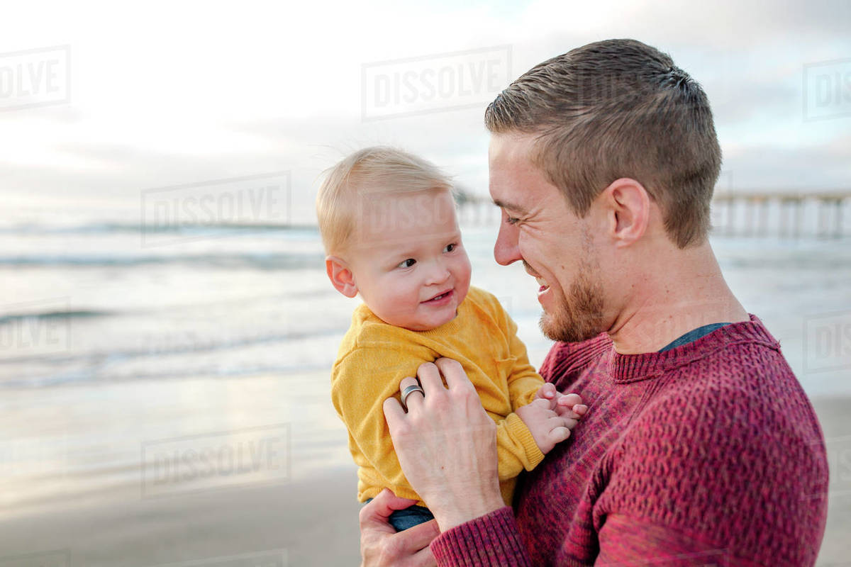 Laughing dad holding smiling baby at the ocean near Scripps Pier Royalty-free stock photo