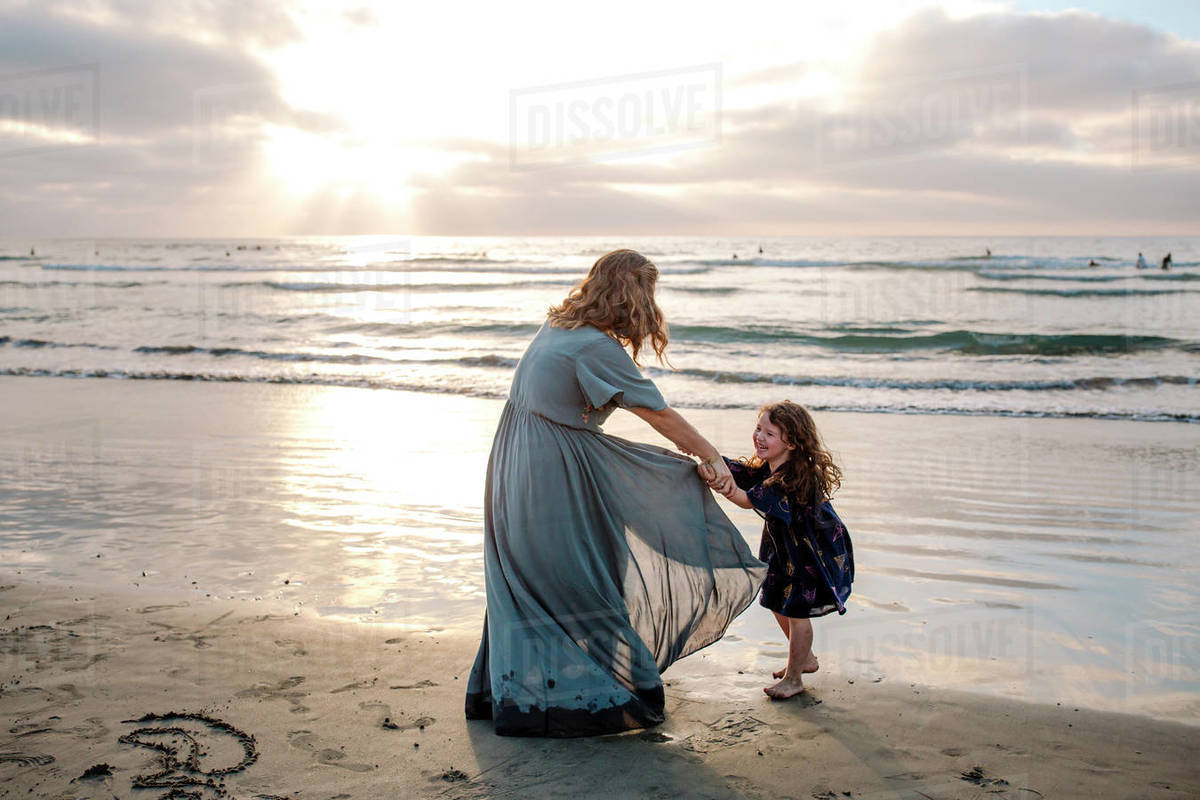Mom in long dress playing with 3 yr old daughter on beach at sunset Royalty-free stock photo