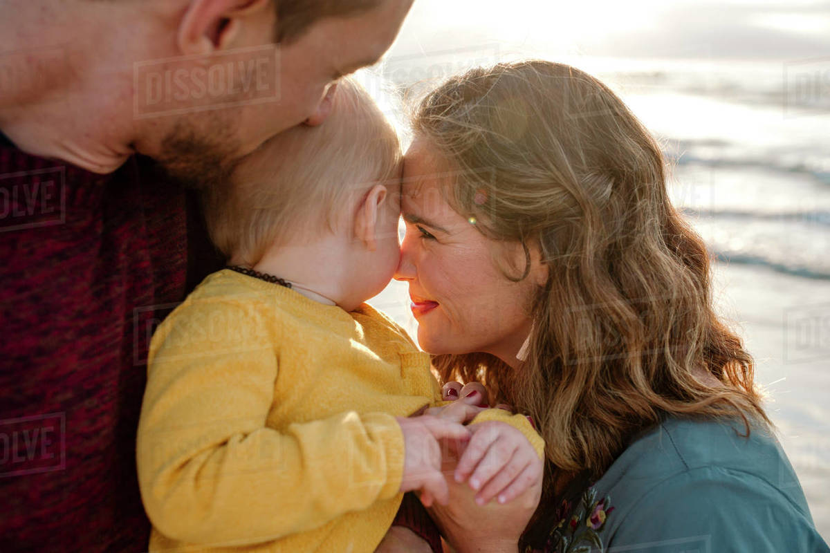 30 yr old parents lovingly snuggle 6 mo old baby at the ocean Royalty-free stock photo