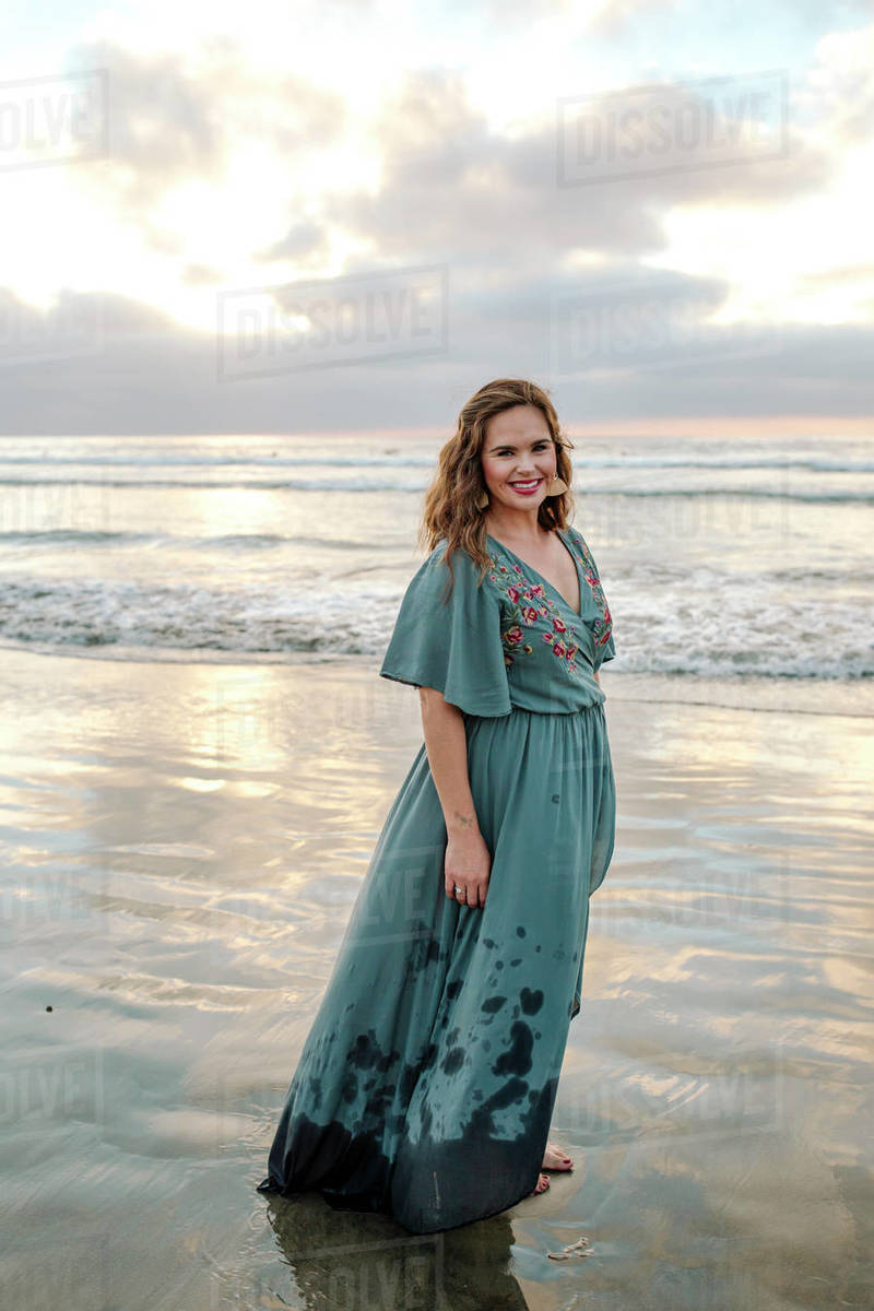 Beautiful barefoot woman in long blue dress standing on beach Royalty-free stock photo
