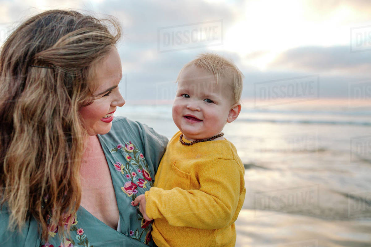 Glowing 30 yr old mom holds happy 6 mo old baby at ocean at sunset Royalty-free stock photo