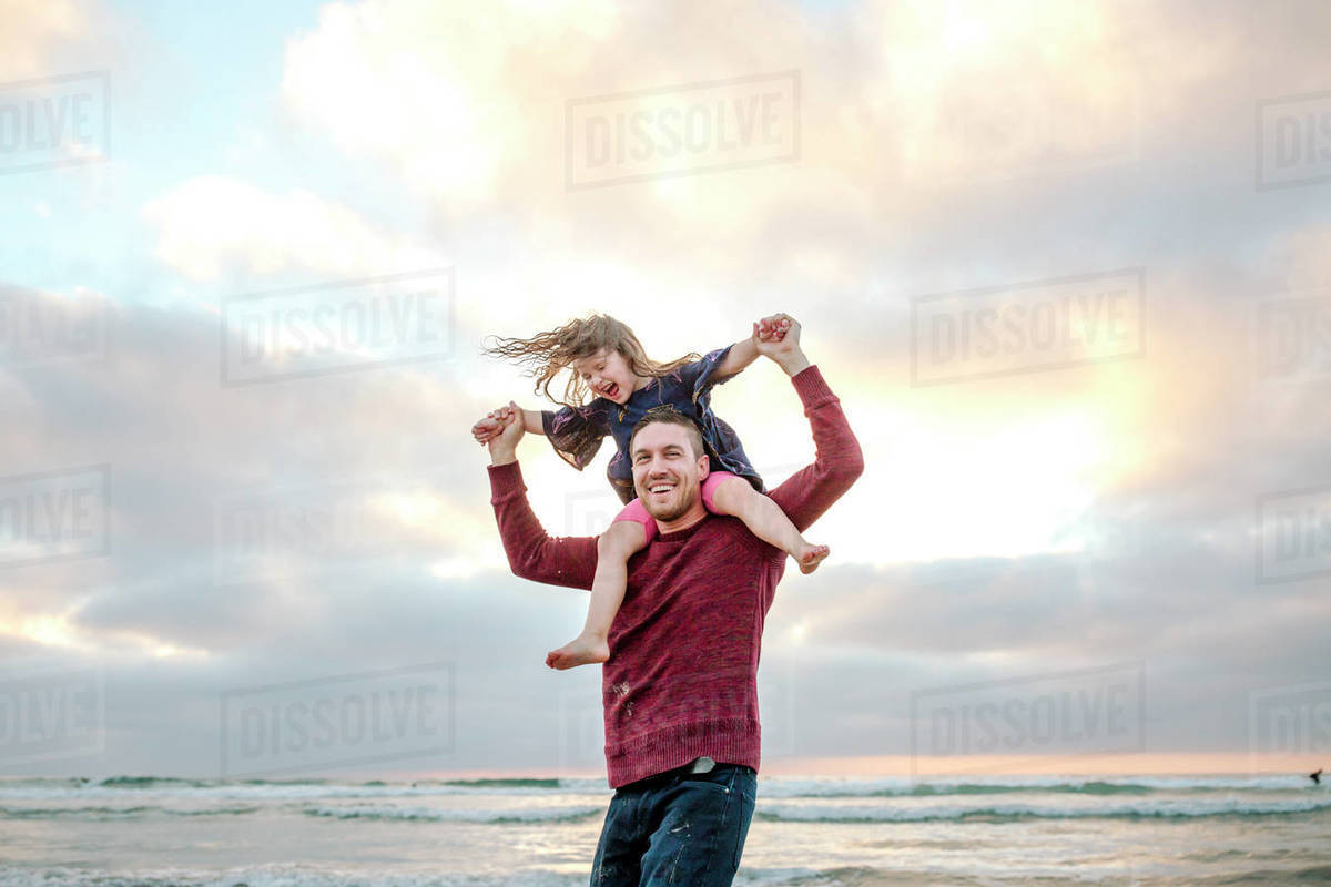 Laughing 3 yr old girl on dad's shoulders by ocean at sunset Royalty-free stock photo