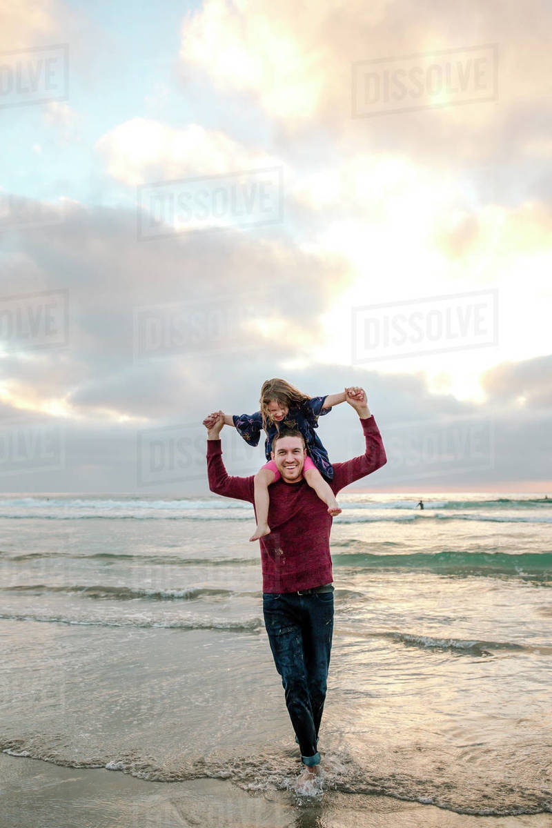 Dad standing in surf with laughing daughter on shoulders at sunset Royalty-free stock photo
