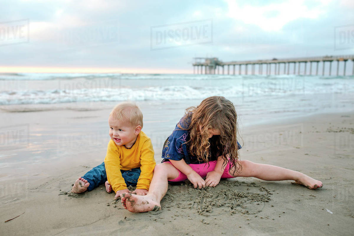 Young girl and baby brother playing in sand on beach near ocean pier Royalty-free stock photo