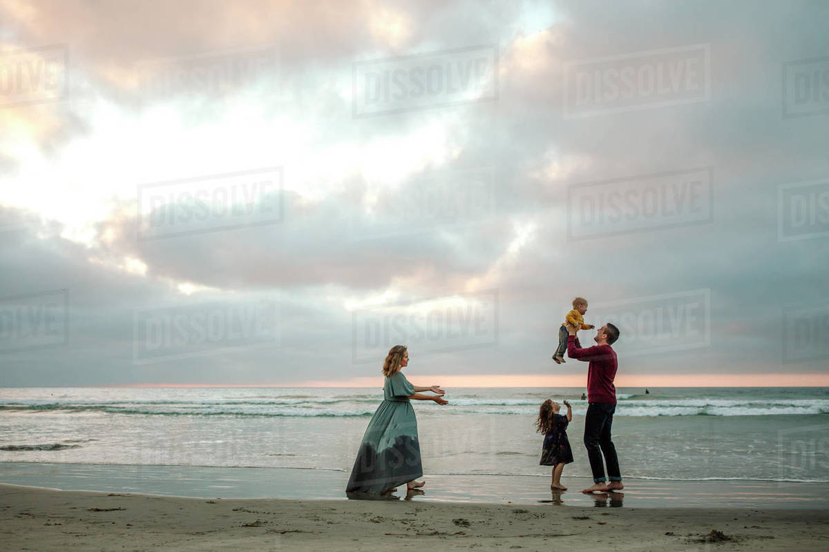 Young parents with two children playing in the ocean surf at sunset Royalty-free stock photo