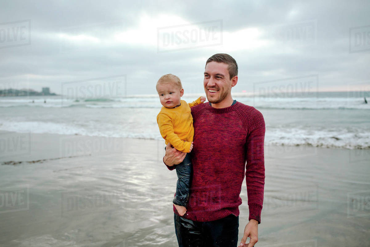 Smiling 30 yr old dad in red sweater holding baby at the ocean Royalty-free stock photo