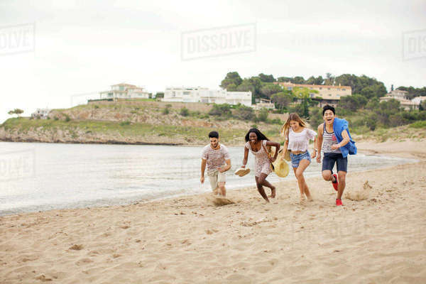 Playful friends running on shore at beach during vacation Royalty-free stock photo