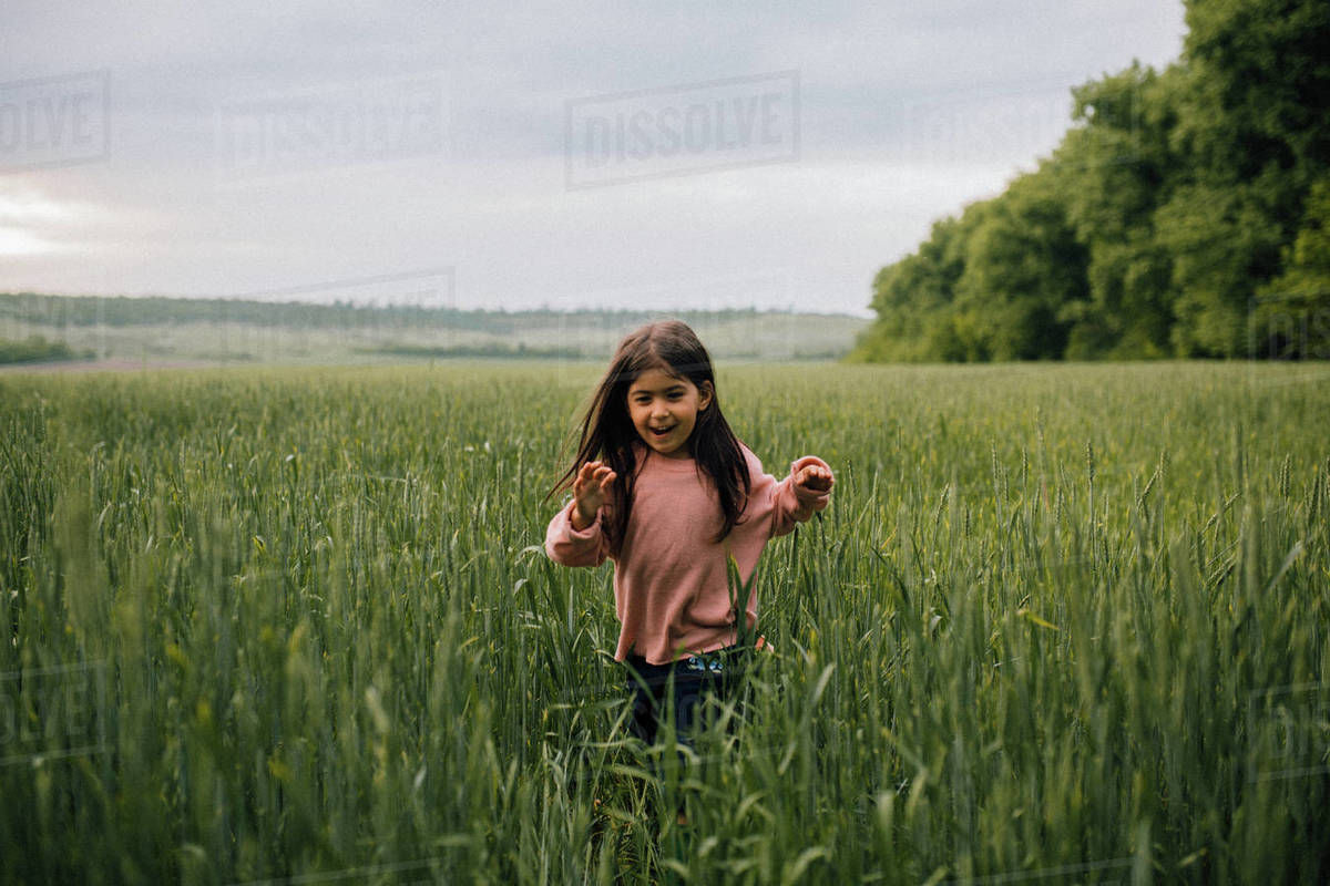 Laughing child running through field at dusk Royalty-free stock photo