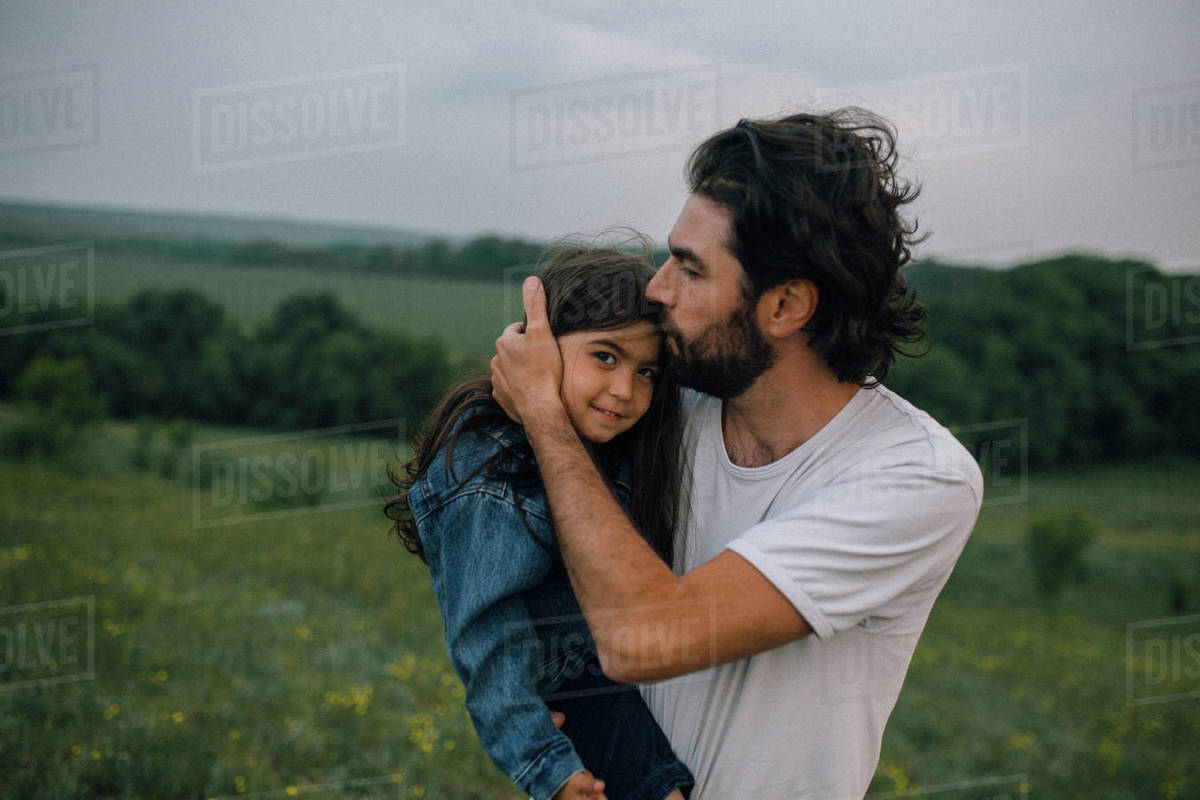 Father carrying and kissing daughter outdoors in field Royalty-free stock photo