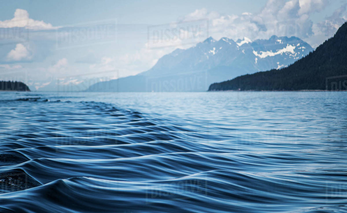 A boat's wake causes ripples and shapes on the water surface in Alaska Royalty-free stock photo