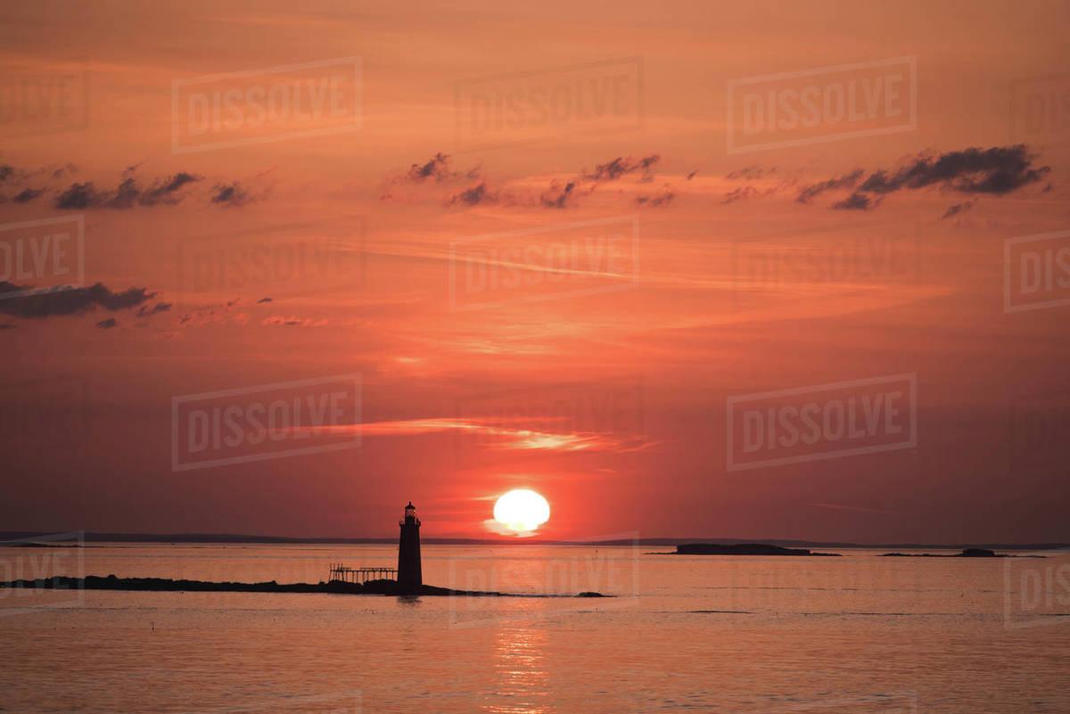Sunrise over an island lighthouse off the coast of Maine Royalty-free stock photo