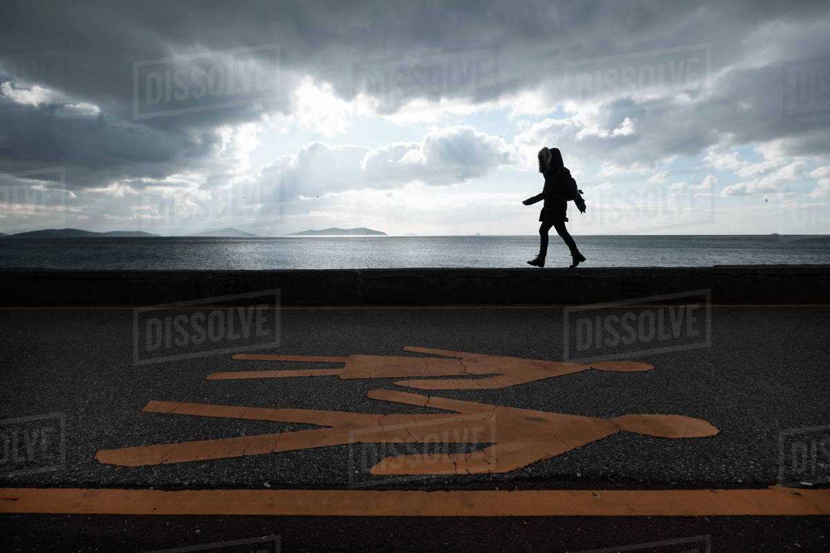 Woman walking in the park near the sea Royalty-free stock photo