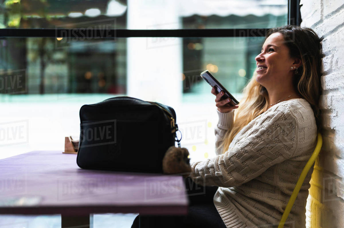 Happy woman using voice recognition on her phone Royalty-free stock photo