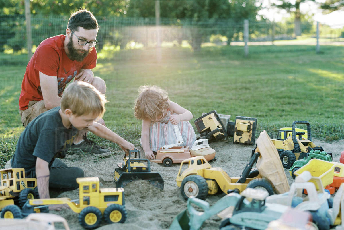 A father and his children playing in a sandbox with trucks together Royalty-free stock photo