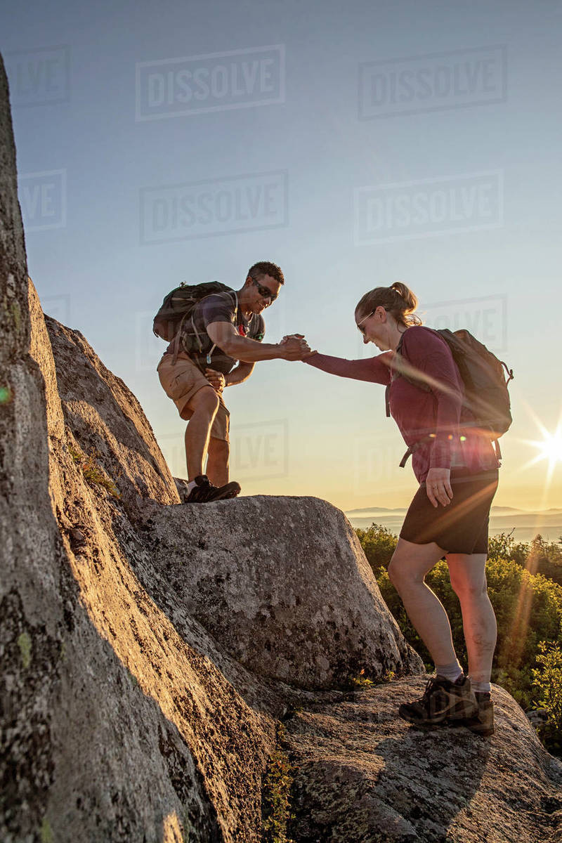 African American male helps female hiker up ledge on mountain in Maine Royalty-free stock photo