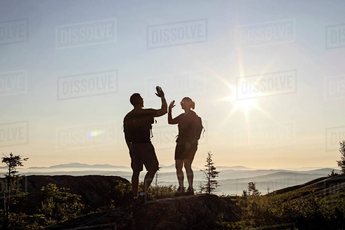Two hikers high five and celebrate reaching summit of mountain, Maine Royalty-free stock photo