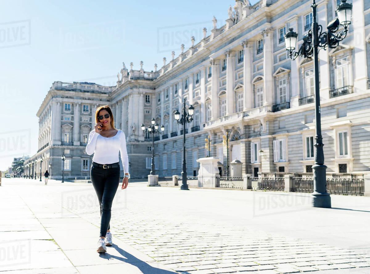 Woman walking through the city while talking on the phone Royalty-free stock photo