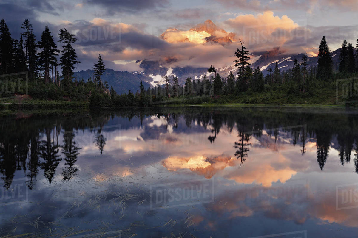 Reflection of mountain, clouds, trees at sunset Royalty-free stock photo