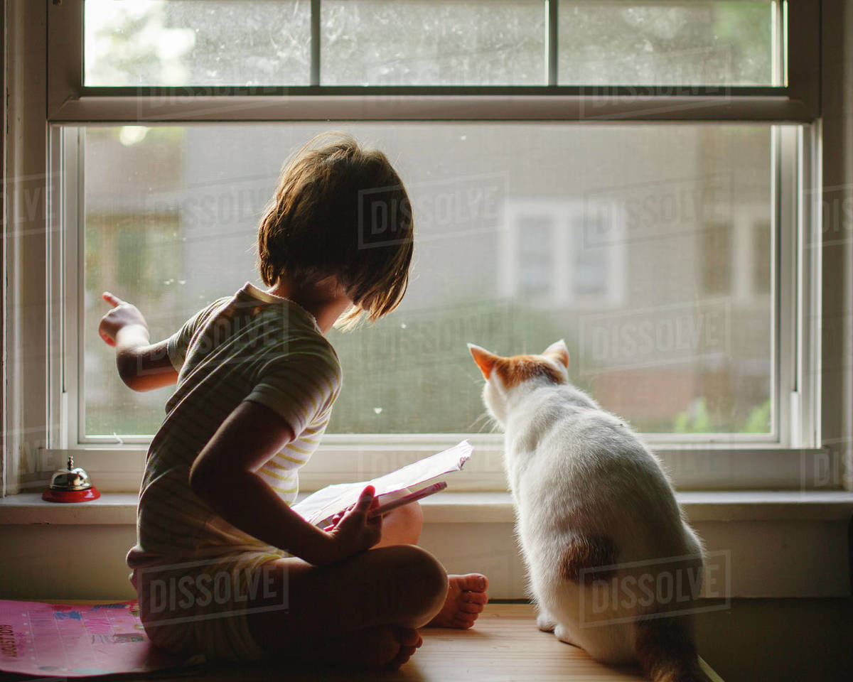 A little girl sits on a bench with a cat looking out window together Royalty-free stock photo