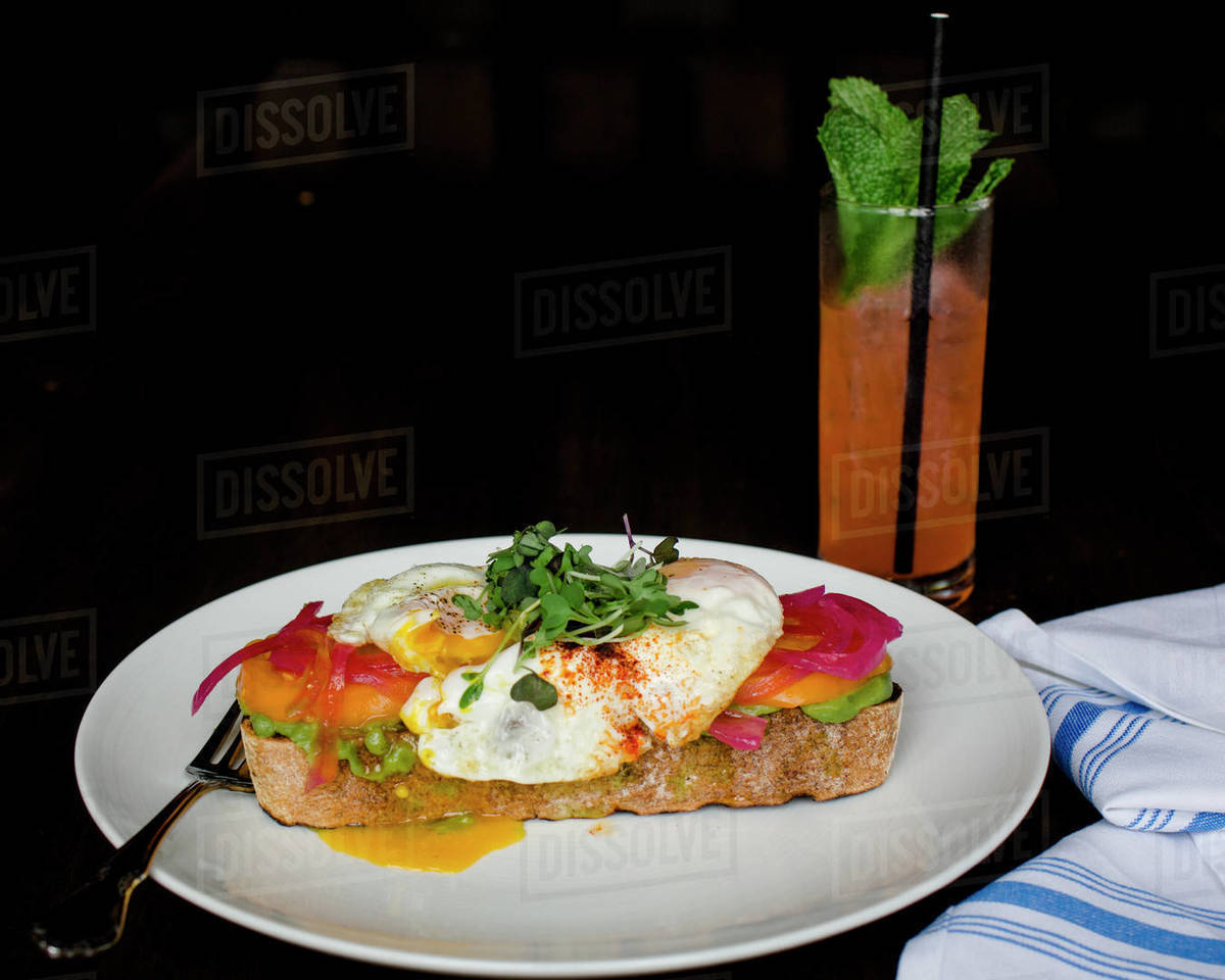 Open-faced egg sandwich and cocktail with mint on dark background Royalty-free stock photo