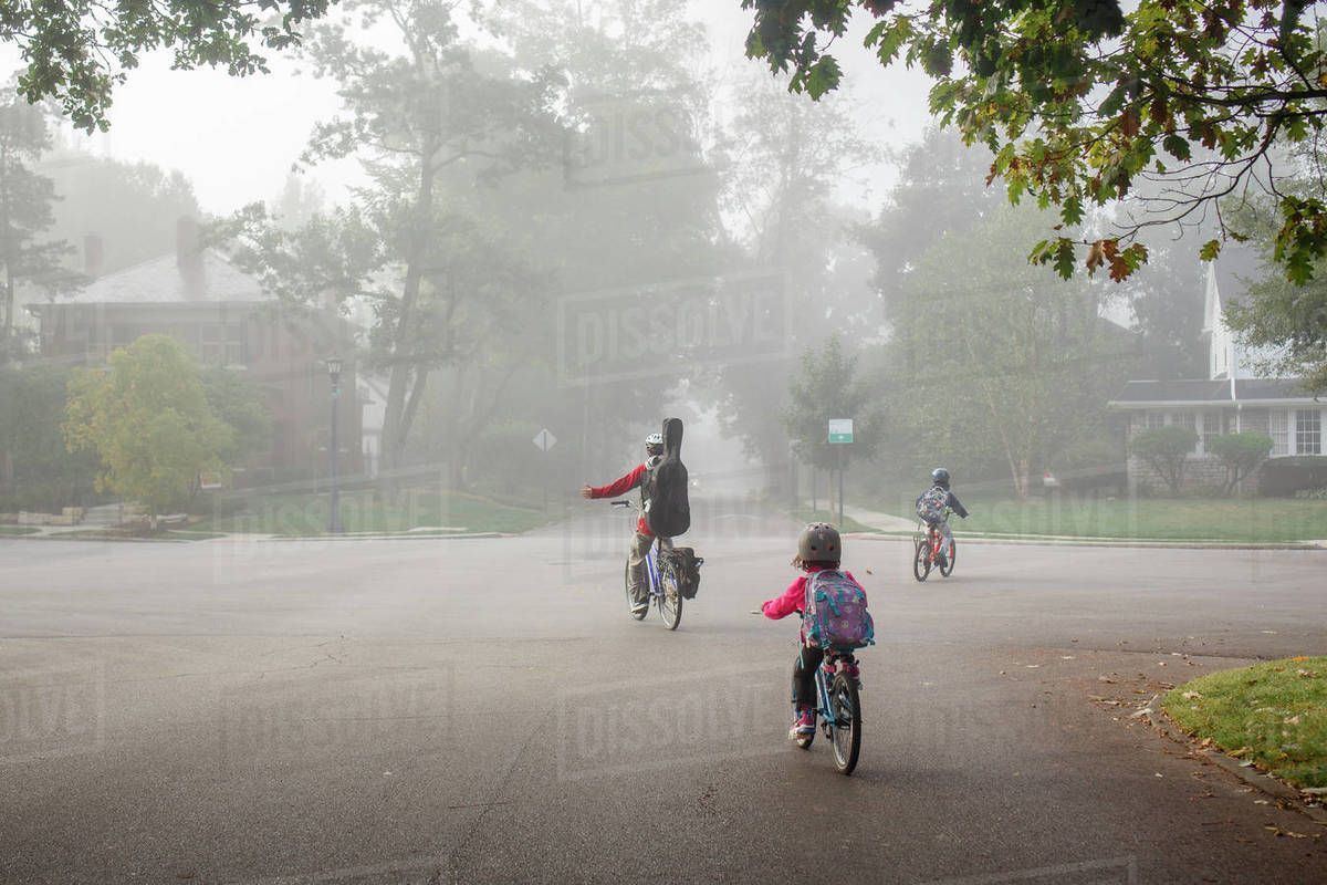 A family bikes to school together on foggy street with backpacks on Royalty-free stock photo