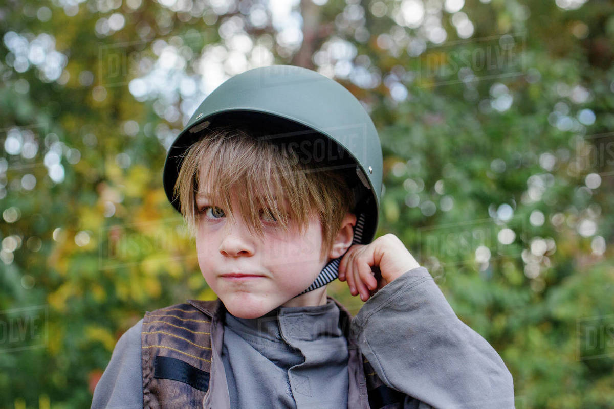 A boy dressed in a soldier costume tugs at the strap of his helmet Royalty-free stock photo