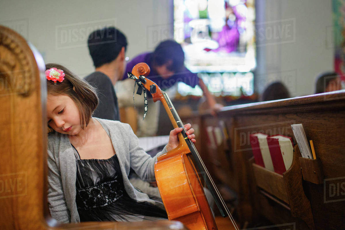 A small girl in fancy dress sits in a church pew holding a cello Royalty-free stock photo