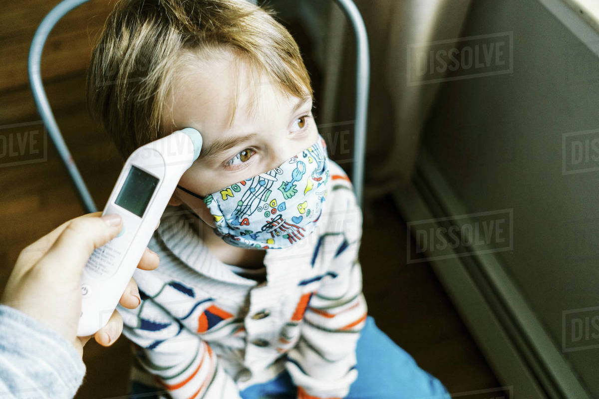 Child with fever wearing mask in home getting temperature taken Royalty-free stock photo