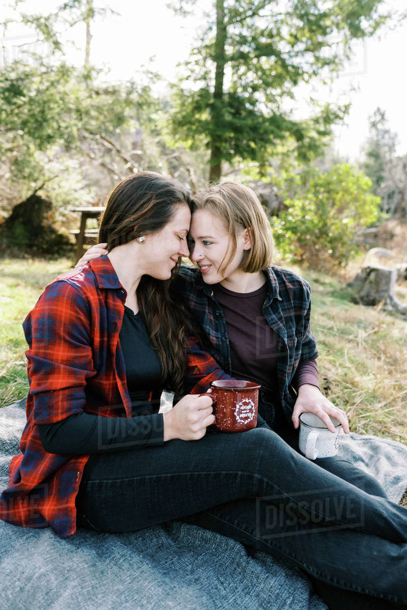 Cute couple sitting on blanket after hike drinking coffee from thermos Royalty-free stock photo