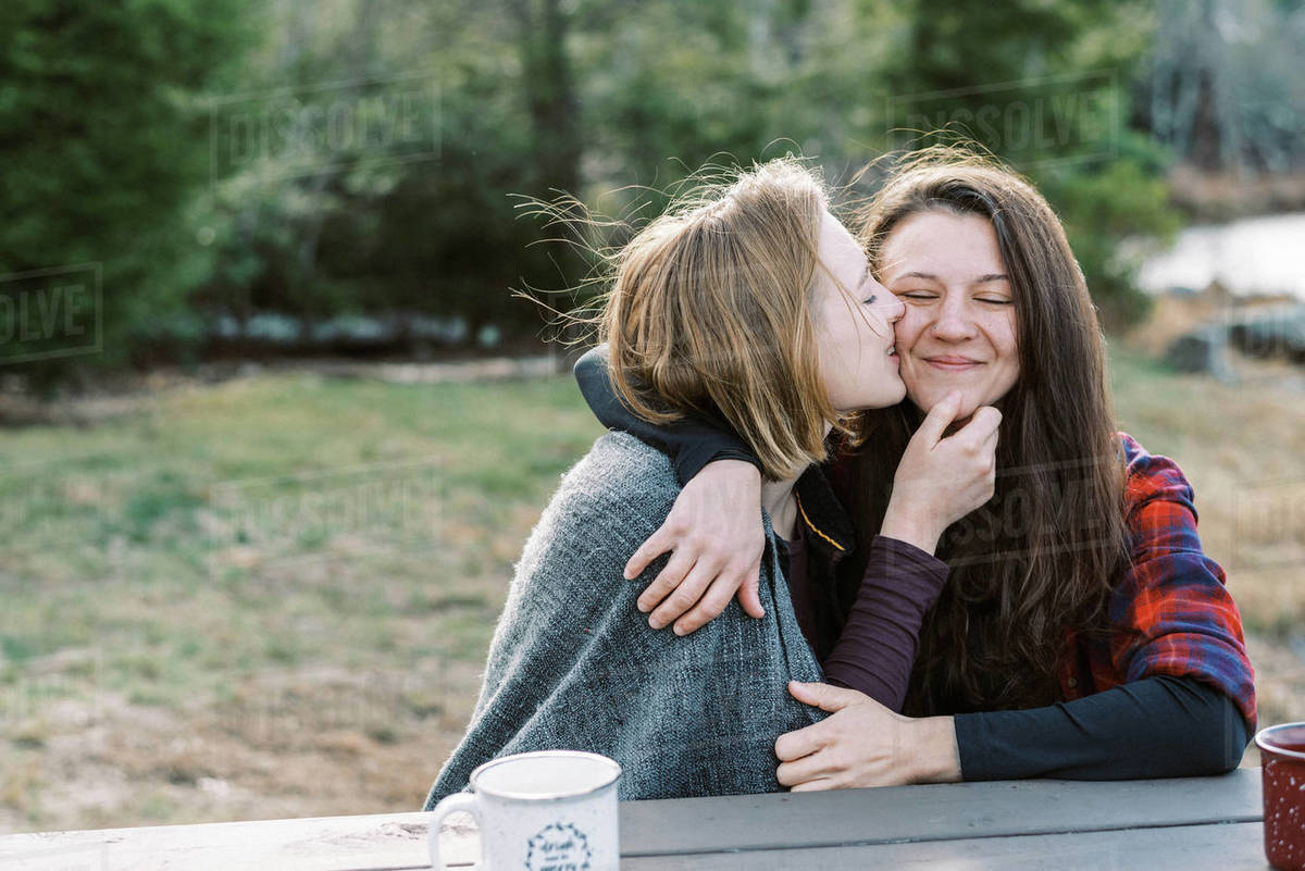 Young lesbian couple cuddling under blanket after hike Royalty-free stock photo