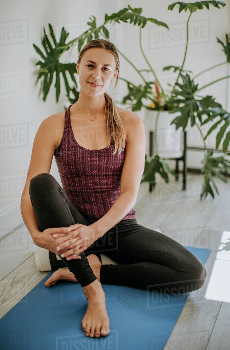 Portrait of young fit white woman sitting on yoga mat indoors Royalty-free stock photo