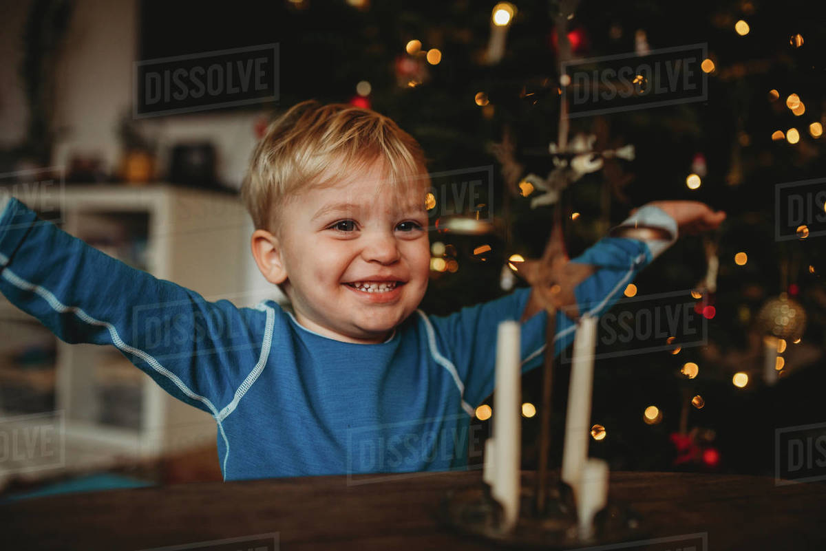 Happy boy smiling at home with a Christmas tree behind him Royalty-free stock photo