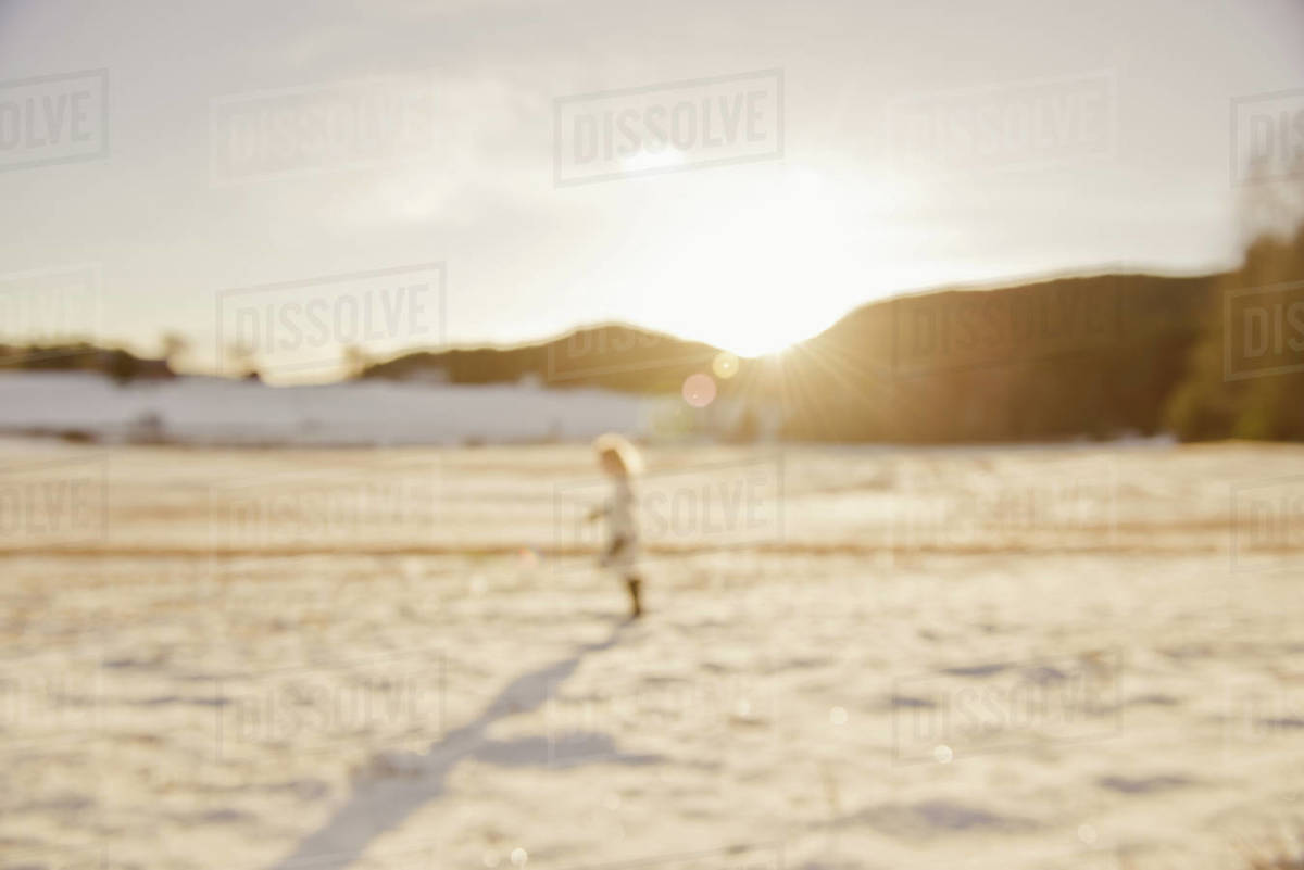 Blurry photo of child running in snowy field with golden sunset behind Royalty-free stock photo
