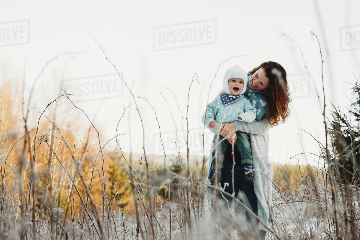 Mother holding child in arms on a sunny day in frosted field winter Royalty-free stock photo