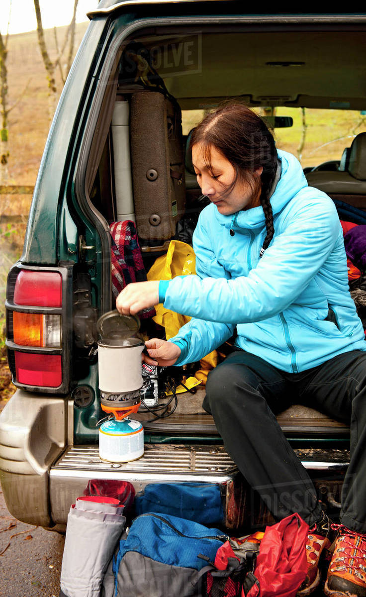 Woman boiling water on camping stove at the back of her car Royalty-free stock photo
