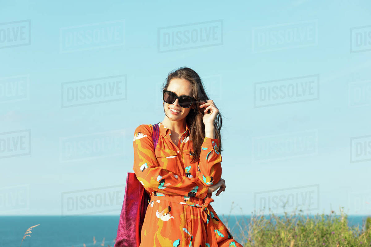 Young woman with long hair and flowery fashion orange dress posing by Royalty-free stock photo