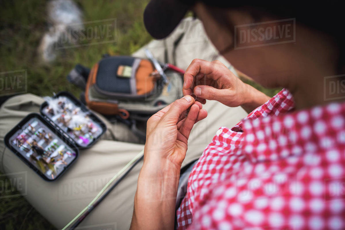 Woman angler ties fly onto end of fly fishing line while sitting Royalty-free stock photo