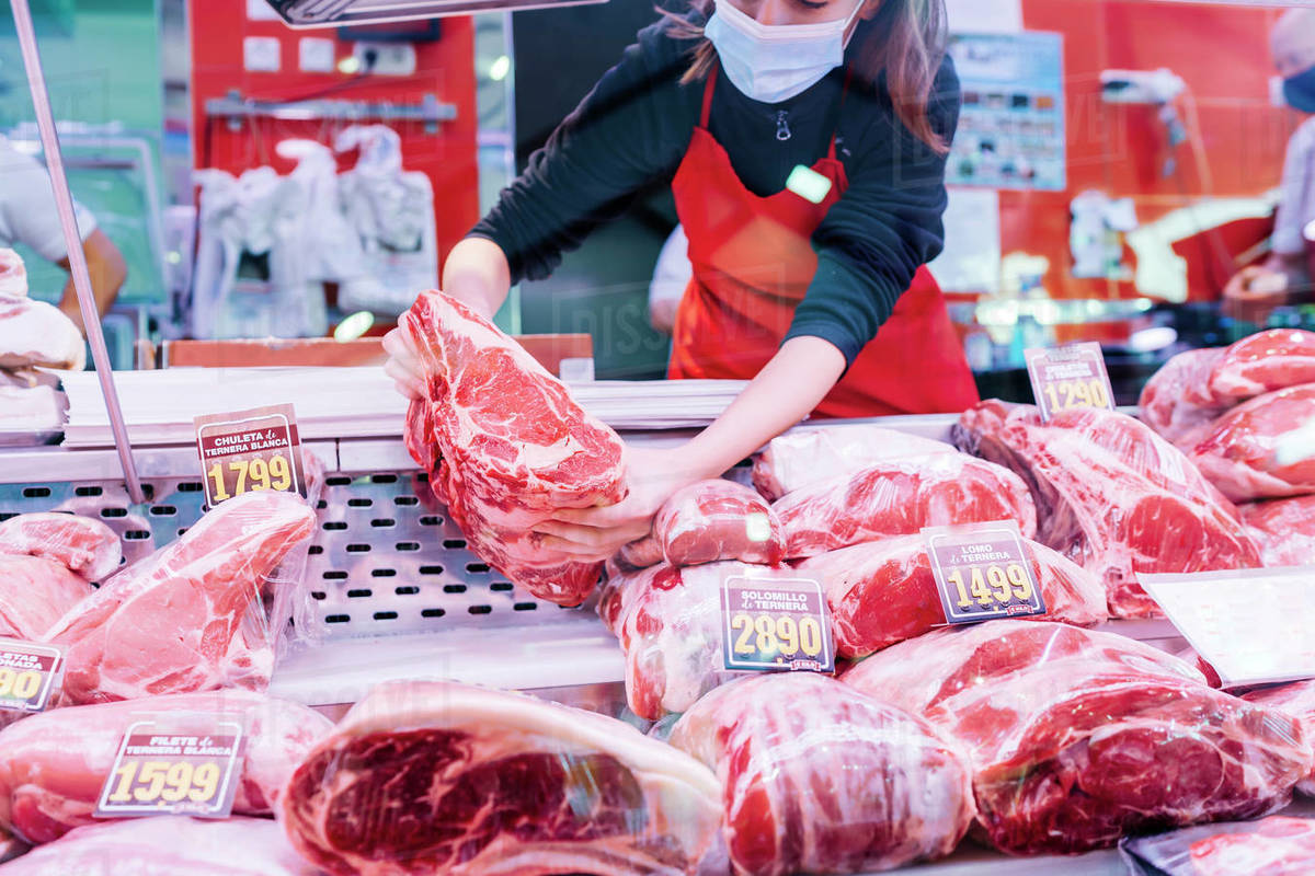 Butcher woman placing meat on the counter Royalty-free stock photo