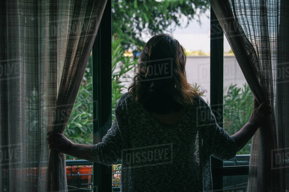 A Woman On The Balcony And Looking Down The Street. COVID-19 Royalty-free stock photo