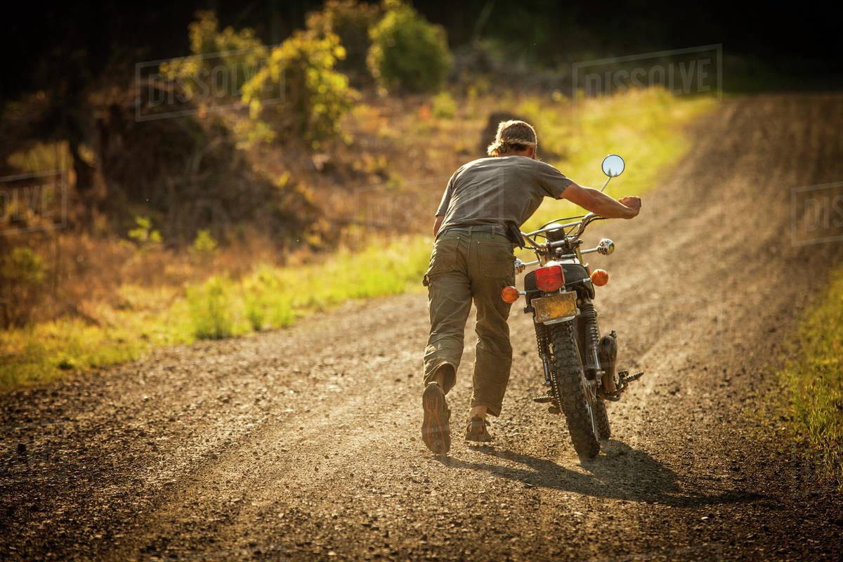 Man pushing motorcycle - Stock Photo - Dissolve