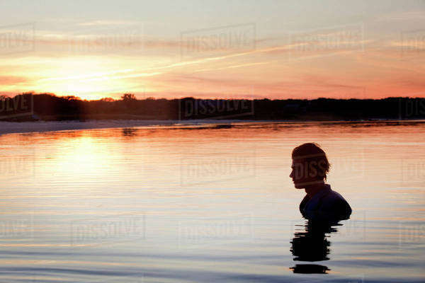 Silhouette of businessman standing in neck deep waters at sunset Royalty-free stock photo