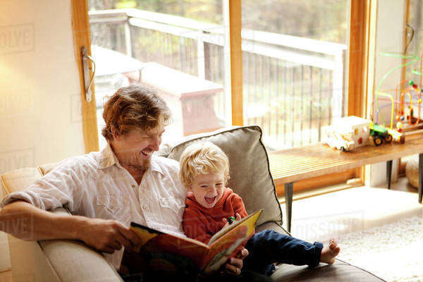 Father and son ( 2-3 ) reading on sofa Royalty-free stock photo
