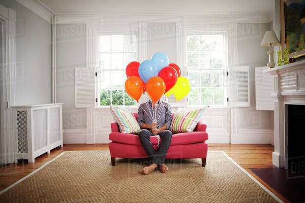 Man sitting on couch with balloons Royalty-free stock photo