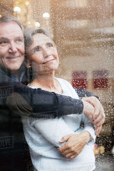 Loving senior couple looking through wet window Royalty-free stock photo