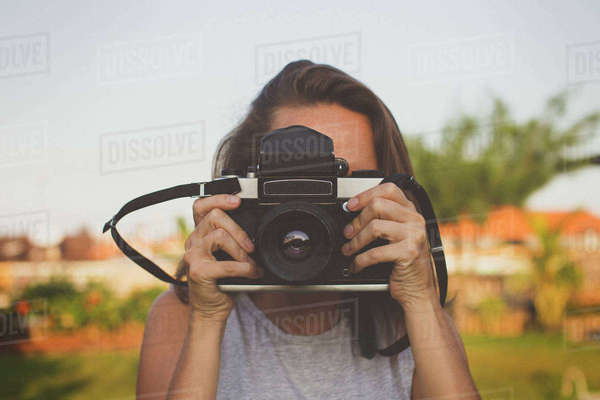 Woman photographing through old-fashioned camera Royalty-free stock photo