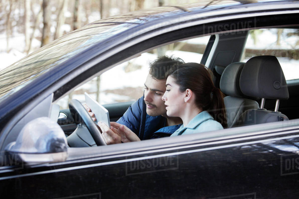 Young couple using tablet for car navigation stock photo